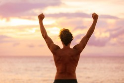 Happy strong man with arms up in success. Silhouette of fit male athlete winner from behind standing at ocean beach raising arms in happiness.