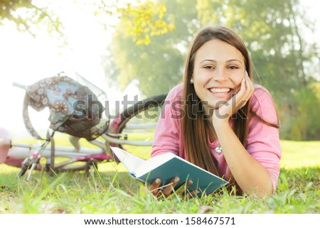 Happy student girl relaxing on green grass reading book.Bicycle in the background.