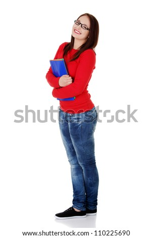 Happy student girl wearing jeans, red blouse and black glasses is holding folders. Smiling young woman standing with crossed legs, isolated on the white background.