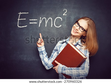 Happy student girl with book and glasses has written on the blackboard formula in physics