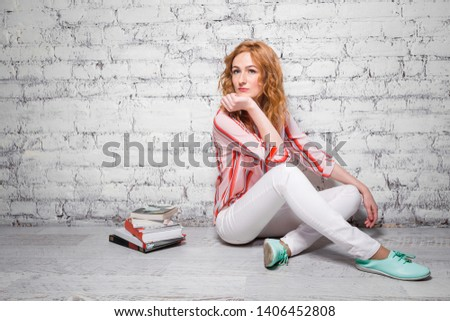 happy student girl with red hair and freckles prepares homework, prepares for homework sitting on the floor near a white brick wall.