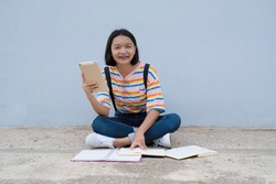 Happy student hold laptop sitdown with many book at school  ,blue wall background.
