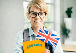 Happy Student in glasses with English textbooks and British flag