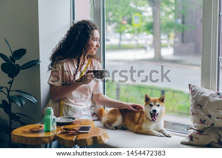 Happy student pretty girl is stroking adorable shiba inu dog sitting in cafe on window sill with cup of tea and enjoying leisure time. People and relaxation concept.