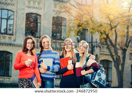 Happy student\'s life! Group of smiling young women standing together outdoors looking at camera