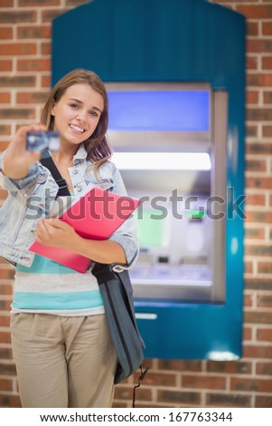 Happy student standing showing her card to camera at the atm in college