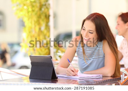 Happy student studying and learning taking notes with a digital tablet in a coffee shop