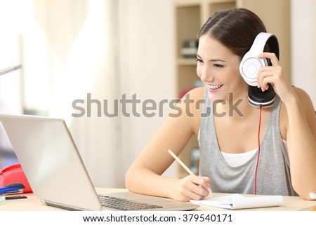 Happy student studying watching video lecture on line and listening with headphones and taking notes sitting in a desktop at home
