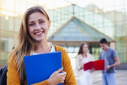 Happy student with folder next college on the background of friends. Education concept