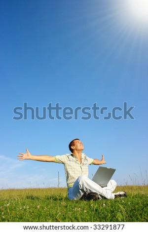 Happy student with laptop on green meadow, sunny day