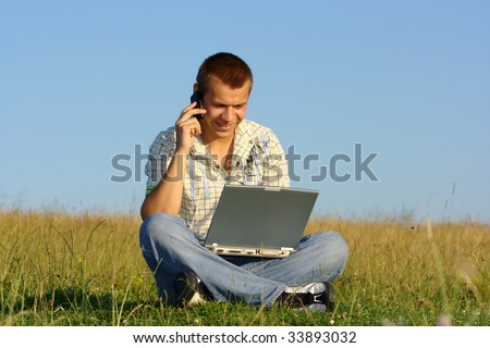 Happy student working with laptop and talking to a cell phone on green meadow, summer sunny day