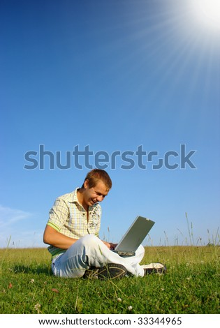 Happy student working with laptop on green meadow, summer sunny day