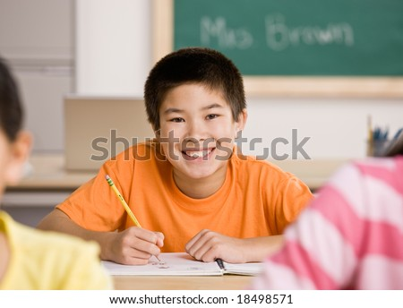 Happy student writing in notebook in school classroom