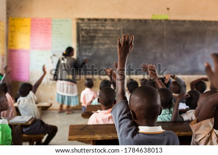 Happy students at a school in Uganda, Africa.  Students raising their hands.