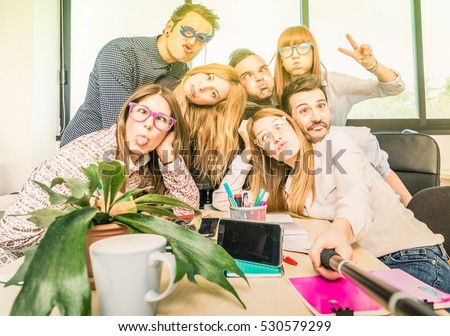 Happy students employee workers group taking selfie with stick - University concept of human resource on working fun time - Startupper at college office - Bright contrasted filter with sunshine halo
