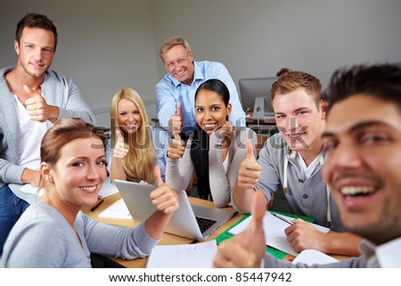 Happy students holding thumbs up in university