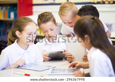 Happy students in classroom using a digital tablet, they are all wearing uniforms.