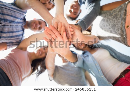 Happy students putting their hands together at the university #245855131