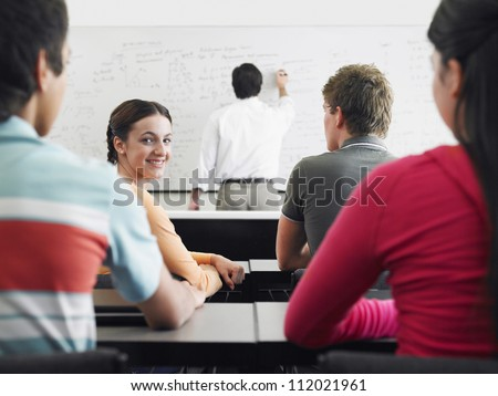 Happy students studying with professor in classroom