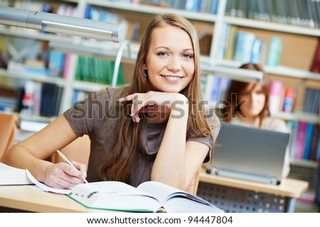 Happy Studying young teenage college student girl in a library with book