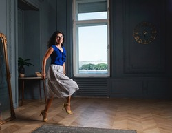Happy stylish beautiful longhaired woman a blue shirt and skirt in glasses jumping in a room with modern appartment interior and looking at camera. The wind blows through the girls hair