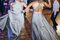 happy stylish bride and bridesmaids dancing and having fun at wedding reception in restaurant. guests dancing in light, people in motion at party in club. fun moments.