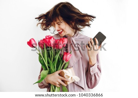 happy stylish girl smiling and dancing with phone and holding pink tulips and gift box on white background. happy mothers or womens day concept. emotional moment of happiness #1040336866