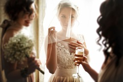 happy stylish gorgeous blonde bride with bridesmaids on the background  hotel room