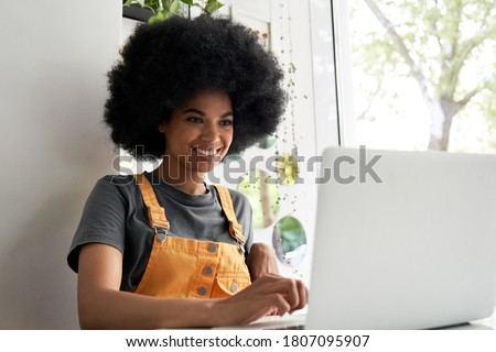 Happy stylish hipster African American female student with Afro hair using laptop computer sitting at table at home office, in cafe, remote studying or working in internet, watching online content.