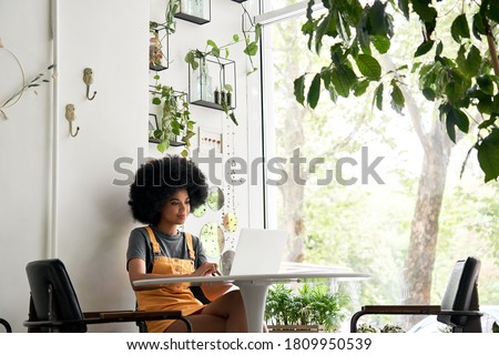 Happy stylish hipster African American female student with Afro hair using laptop computer sitting at table learning at home, in cozy modern cafe, remote studying, watching video, working in internet.