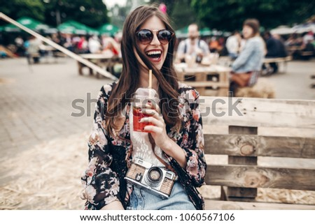 happy stylish hipster woman in sunglasses with lemonade, smiling. boho girl in denim and bohemian clothes, holding cocktail sitting on wooden bench at street food festival. summertime