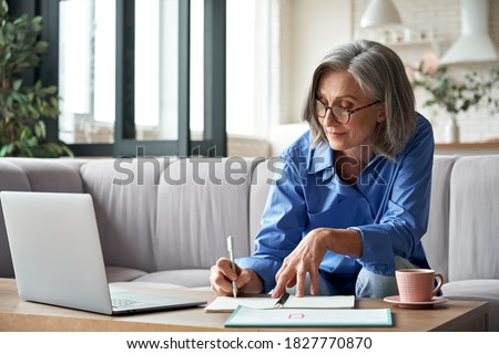 Happy stylish mature old woman remote working from home distance office on laptop taking notes. Smiling 60s middle aged business lady using computer watching webinar sit on couch writing in notebook.