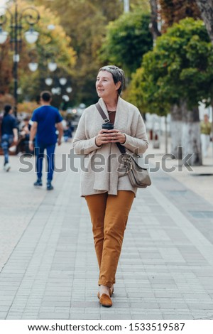 Happy stylish stylish fashionable senior woman dressed in the city streets with a glass of coffee in her hands. anti aging concept
