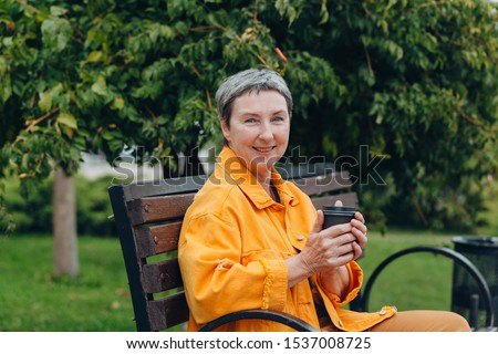 Happy stylish stylish fashionable senior woman dressed in the city streets with a glass of coffee in her hands. anti aging concept #1537008725