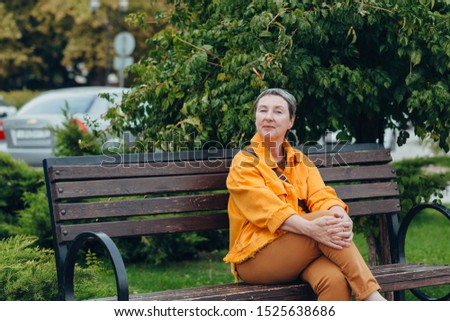 Happy stylish stylish fashionable senior woman sitting on a bench in the city streets. anti aging concept