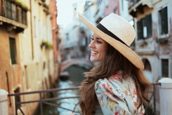 happy stylish tourist woman in floral dress with hat sightseeing in Venice, Italy.