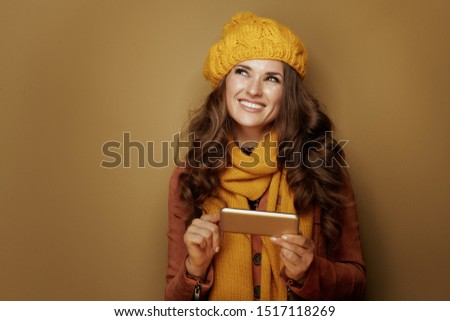 happy stylish woman in yellow beret and scarf with smartphone communicating in social media and against bronze background.