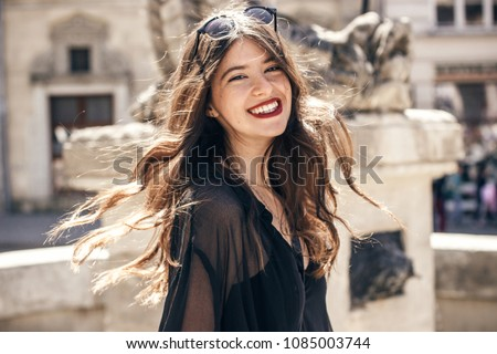 happy stylish woman smiling in sunlight in european city street. beautiful hipster girl in fashionable outfit, waving hair and relaxing. luxury look. carefree and true happiness concept