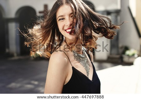 happy stylish woman waving hair in sunlight at old european city street, luxury look, space for text, moment of carefree and true happiness