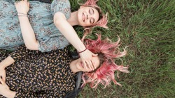 Happy stylish woman with pink hair in blue dress lies on grass and covers with palm her face of friend in black fashionable dress with floral print.Two pink-haired trendy girls enjoy on lawn in nature