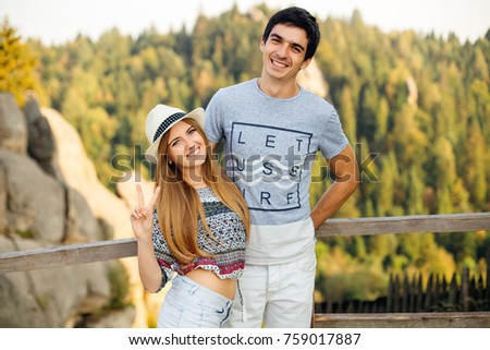 happy, stylish young couple hugging on the background of nature