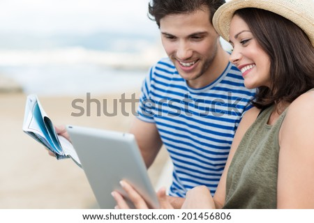 Happy stylish young couple on summer vacation at the beach looking up directions on a tablet computer smiling as they compare a map held by the husband as they plan their sightseeing Stock foto ©