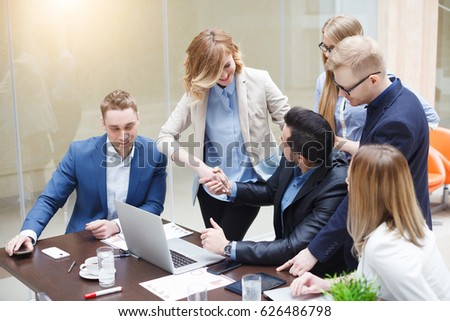 Happy successful business team giving a high fives gesture as they laugh and cheer their success. Signing an important contract, start up concept #626486798