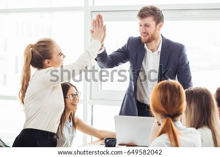 Happy successful business team giving a high fives gesture as they laugh and cheer their success #649582042