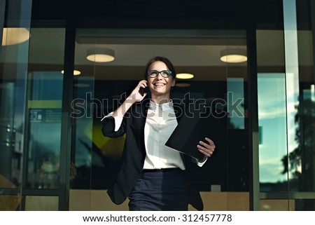 Photo of Happy successful business woman coming out of the office looking at the sun and smiling. Business people concept. Professional manager talking on smartphone with documents in her hands.