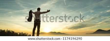 Happy successful businessman celebrating on a wall watching the sunrise silhouetted against the colorful orange sky in a panorama view with copy space. #1174196290