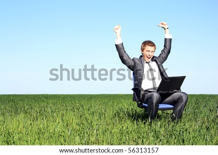 Happy successful businessman.Happy on the green field