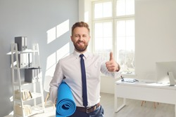 Happy successful businessman in a white shirt with yoga mat standing in the office.