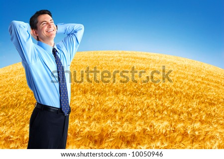 Happy successful  businessman in the field under blue sky