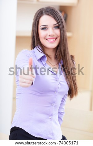 Happy successful businesswoman giving you thumbs up gesture